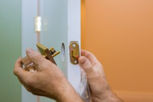 Builder in installing a door lock the door of a new house hand close-up.